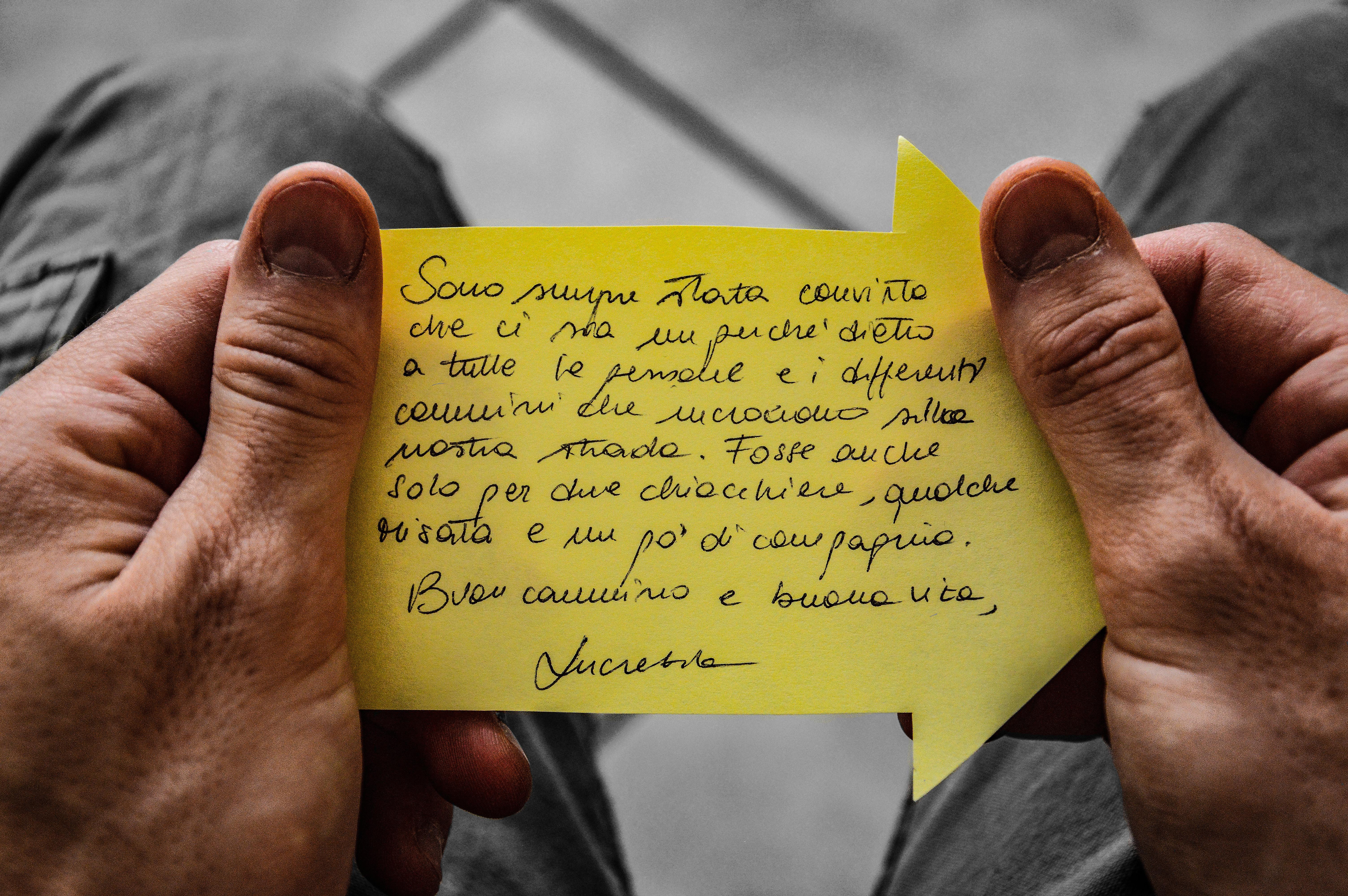messaggio su post it giallo tra le mani