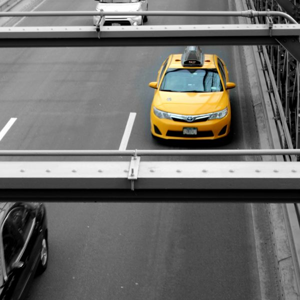 un uomo su una strada con macchine è tutto grigio solo un dettaglio è giallo